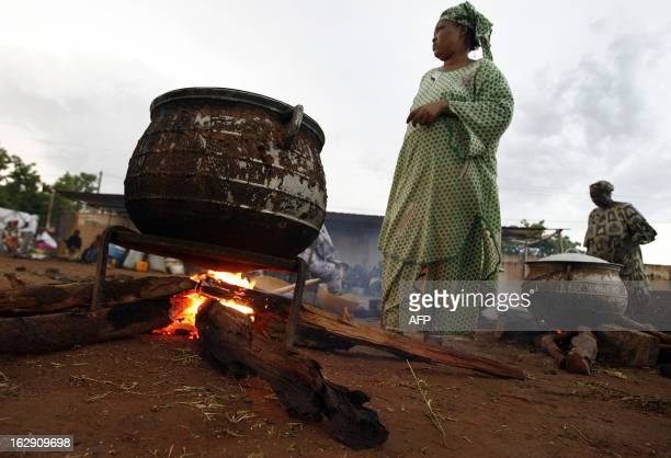 """Women cook 05 June 2007 near the """"Babemba Traore"""" stadium in Sikasso, Mali, after a strong storm destroyed tents used to gather food during a forum..."""