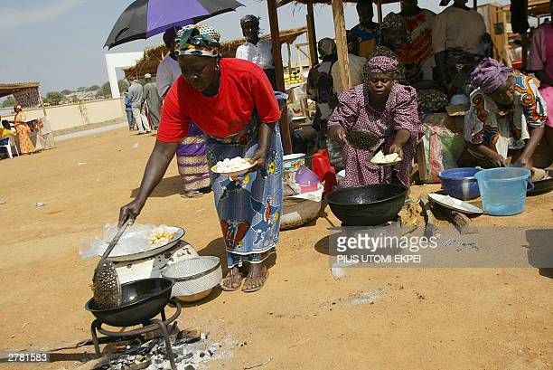 WITH NIGERIAN VILLAGERS REHEARSE THEIR LINES FOR ROYAL MARKET VISIT Women cook a bean cake at a mock market 03 December 2003 arranged at the...