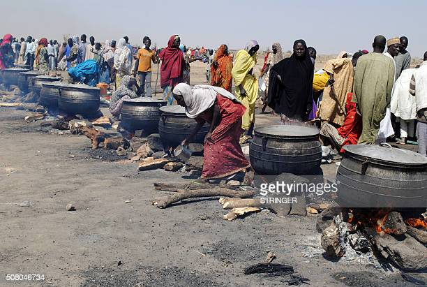 Women cook in pots heated up with firewood at an Internally Displaced Persons camp at Dikwa in Borno State in northeastern Nigeria on February 2 2016...