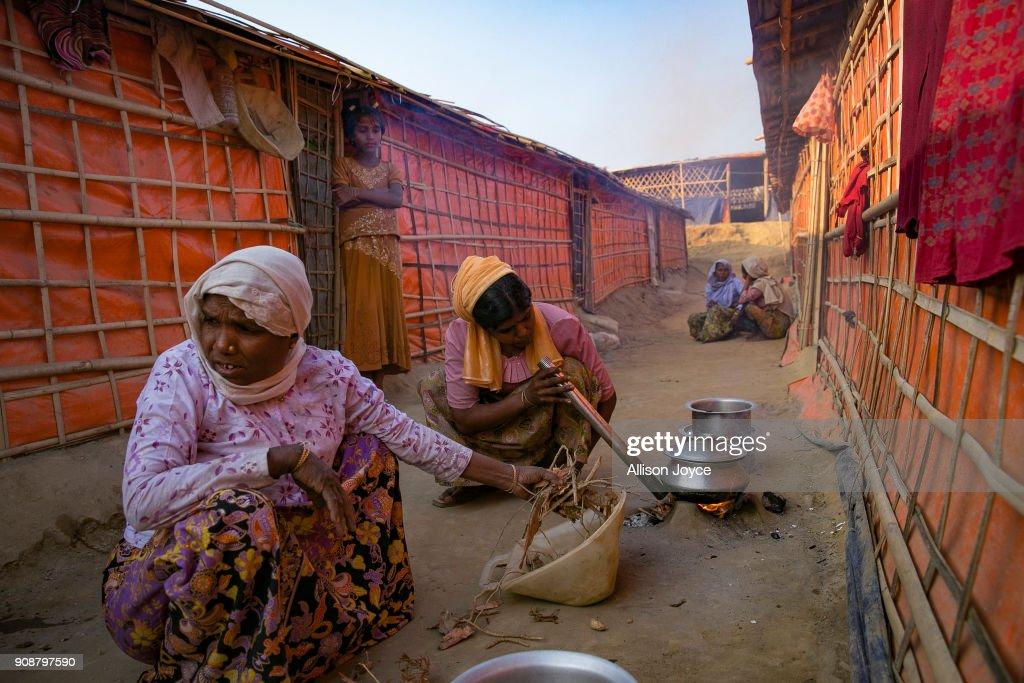 COX'S BAZAR, BANGLADESH - JANUARY 17: Women cook on January 17, 2018 in Cox's Bazar, Bangladesh. In the refugee settlement of Balukhali, over 116 widows and orphans have found shelter within a dense settlement of 50 red tents where no men or boys over the age of 10 years old are allowed. More than 655,000 Muslim Rohingya have crossed the border into Bangladesh since August last year, when they fled Rakhine state after the Myanmar military launched a brutal crackdown which was described by the United Nations as 'ethnic cleansing'. Women and girls reportedly make about 51 percent of the distressed and traumatized Rohingya population in the refugee camps and face a high risk of being victims of human trafficking and sexual abuse, while adolescent girls aged between 13 and 20 risk getting involved in forced marriages. Many of the Rohingya women travelled alone after their husbands had been killed or taken away during the attacks on Rohingya villages as many continue to fear returning home due to the lack of security guarantees.