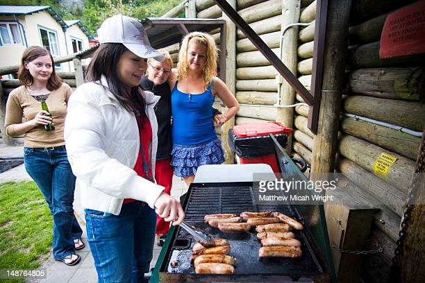Women cooking bbq sausages at hostel.