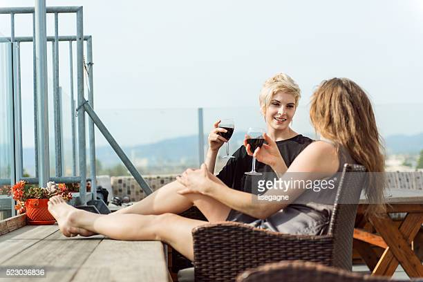 women couple relaxing on the roof - terraced field stock pictures, royalty-free photos & images