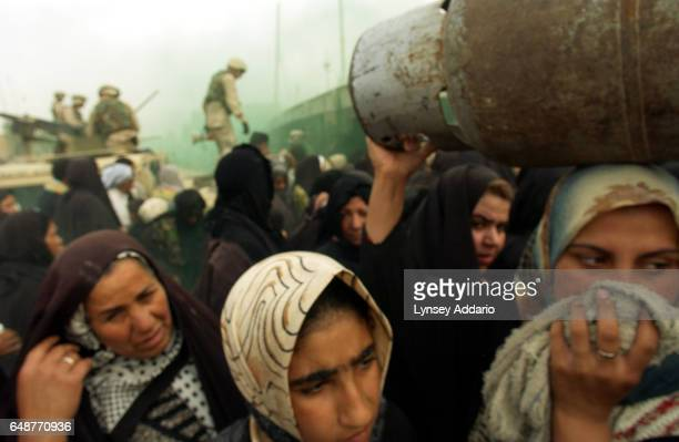 Women cover their faces after American soldiers from the First Cavalry Division fire gas onto a desperate crowd during a propane distribution in Sadr...