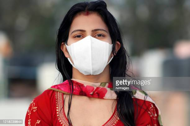 women covering her face with pollution mask for protection from viruses like covid-19 - india stock pictures, royalty-free photos & images