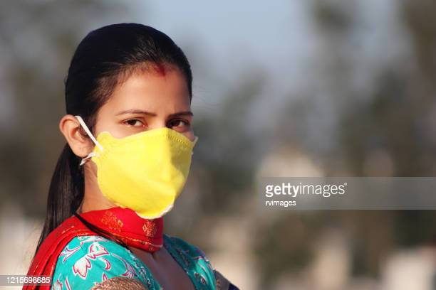 women covering her face with pollution mask for protection from viruses - lockdown stock pictures, royalty-free photos & images