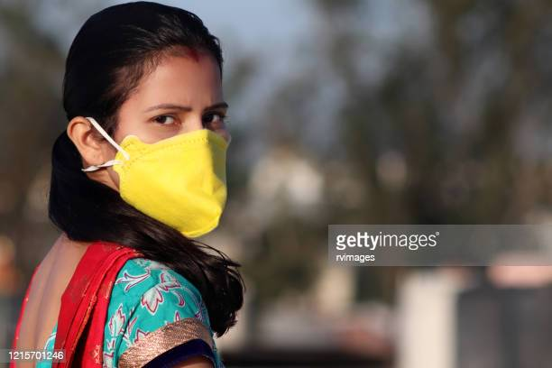 women covering her face with pollution mask for protection from viruses - india stock pictures, royalty-free photos & images