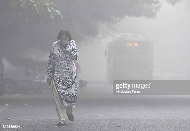 A women covers her face with her hands as she walks amid heavy smog in the early morning at Mayur Vihar area on November 2 2016 in New Delhi India A...