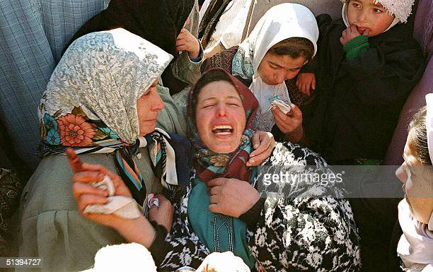 Women cry 11 February 2001 in the shantytown of Cherata near Berrouaghia some 120 kilometers south of Algiers following a massacre that left 27...