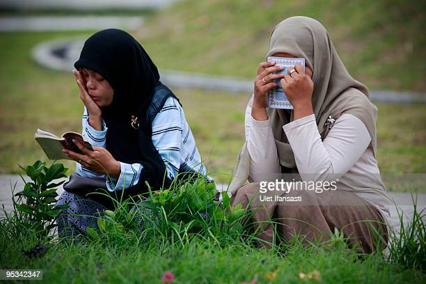 Women cry as they read the Quran at a mass grave site during commemorations on the fifth anniversary of the 2004 Boxing Day earthquake and subsequent...