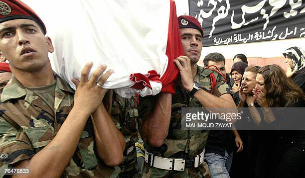 Women cry in mourning as Lebanese soldiers carry the coffin of army officer Ali Nassar during a funeral procession in the village of Kfar Hata south...