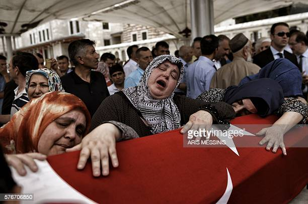 Women cry near the flagdraped coffin of a relative as they mourn in Istanbul on July 17 during the funeral of seven victims of the July 15 coup...