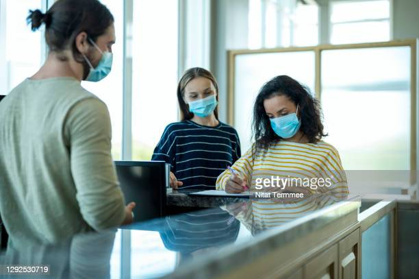 women customer wearing facemask while checking in at gym sport club during spread of the virus. - sport venue stock pictures, royalty-free photos & images