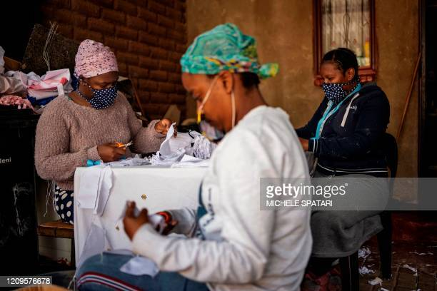 Women cut and sew cotton fabrics into pieces used to manufacture reusable face masks in Johannesburg's Alexandra township, on April 8, 2020. -...