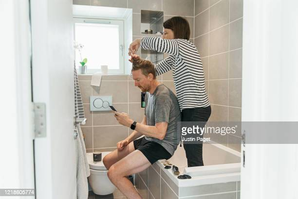 women cutting partner's hair in the bathroom - hairstyle stock pictures, royalty-free photos & images