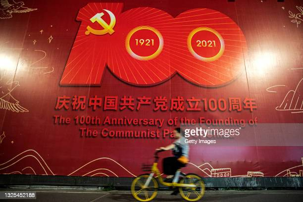 Women cycles past a sign celebrating the centenary of the Chinese Communist Party in street on June 25, 2021 in Wuhan, Hubei. China. With no recorded...