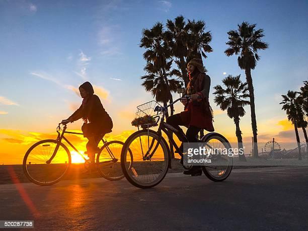 women cycling on santa monica beach, california, usa - santa monica stock pictures, royalty-free photos & images
