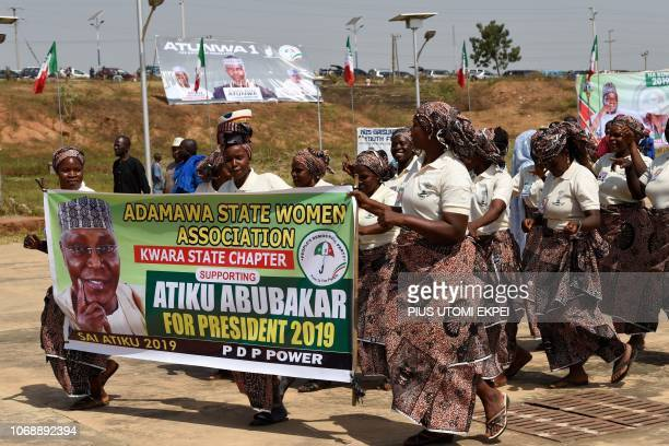 Women dance as they hold a banner picturing Nigeria's opposition party People's Democratic Party presidential candidate Atiku Abubakar during a...