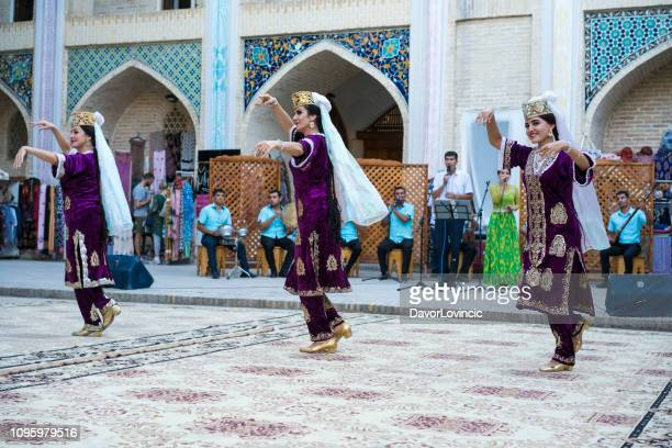 women dancing bukharian music in traditionall dress in bukhara, uzbekistan. - uzbekistan stock pictures, royalty-free photos & images