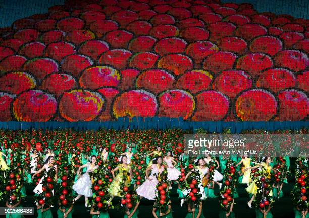 Women dancing in front of apples made by children pixels holding up colored boards during Arirang mass games in may day stadium Pyongan Province...