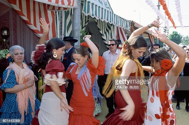 Women dancing in traditional costumes at the Feria de Abril Seville Andalusia Spain
