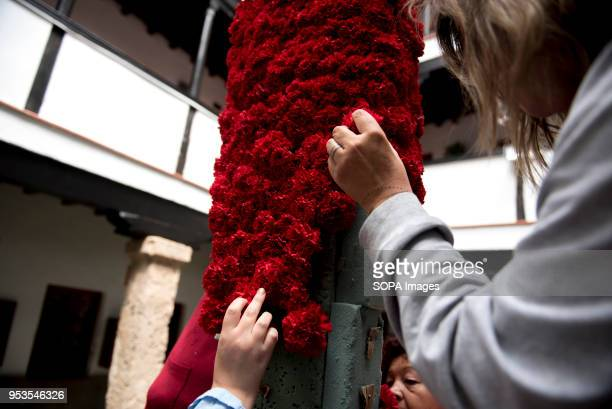 Women decorates with red carnations a cross that will be part of an altar in the 'Día de la Cruz' in Granada El día de la Cruz or Día de las Cruces...