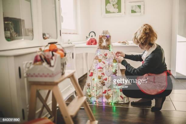 Women decorating christmas tree made of wood