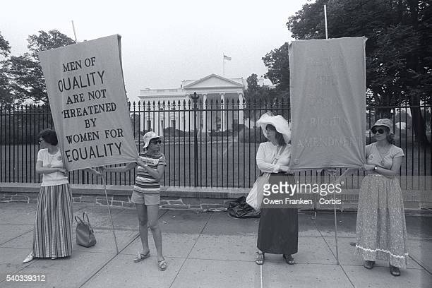 Women demonstrate in support of the passage of the Equal Rights Amendment outside the gates of the White House They hold a sign stating Men of...