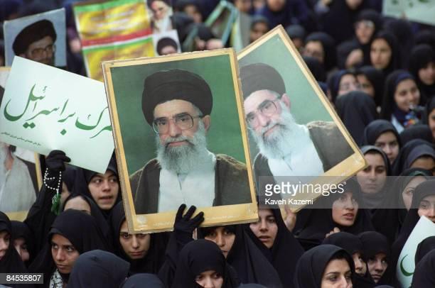 Women demonstrators in black chadors hold portraits of Iran's Supreme Leader Ayatollah Ali Khamenei outside the former American embassy in Tehran on...