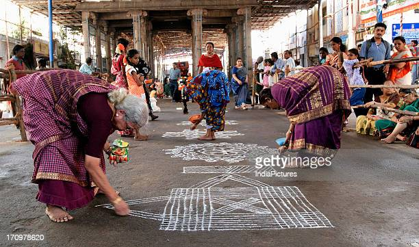 Women designing the floor of Kapaleesvarar temple with rice powder Chennai Tamil Nadu India