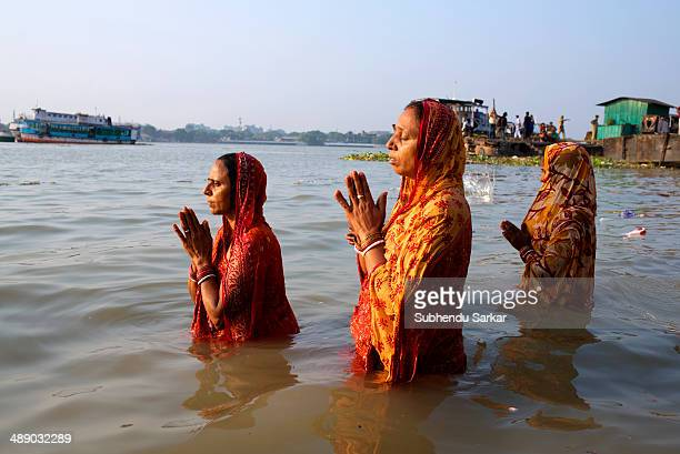 CONTENT] Women devotee stand in the waters of the Hooghly river and pray to the sun during Chhat puja festival in Kolkata India