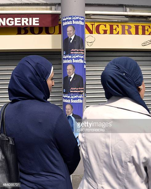 Women discuss near campaign posters for Algerian president Abdelaziz Bouteflika in a street of the Goutte d'Or district of Paris on April 11 2014...