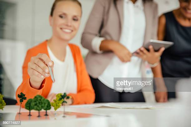 Women discussing modeled trees in meeting room