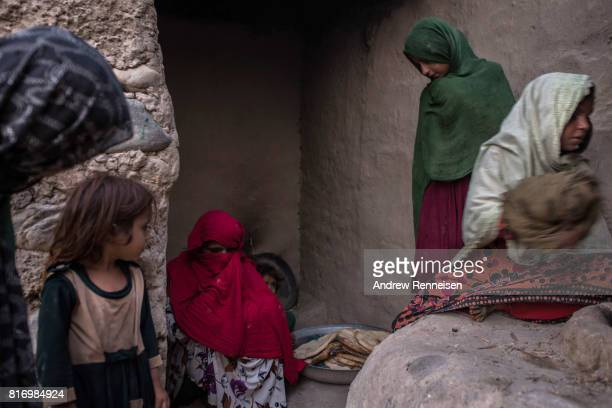 Women displaced by the Islamic State of Iraq and Syria Khorasan bake naan at their current home on July 14 in Surkh Rod District Afghanistan The...