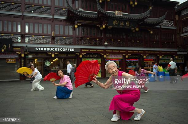 Women do morning exercises in front of a Starbucks restaurant on July 24 2014 in Shanghai Chinese police on July 23 detained five people from a unit...