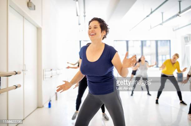 women doing a fitness dance in a class - fat lady in leggings stock photos and pictures