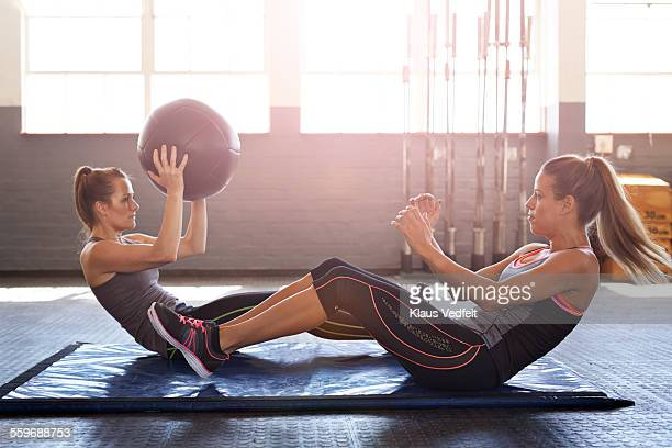 women doing abdominal exercise using ball - sit ups stock photos and pictures