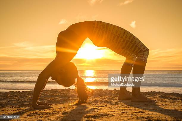 Women Doing Back Bend Yoga Pose By The Sea