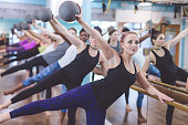 multiethnic group young women do barre