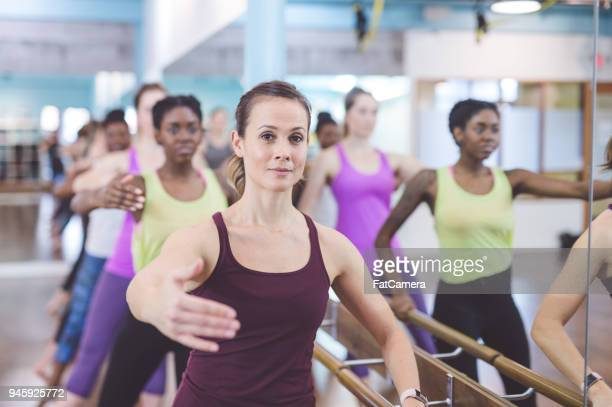 Women Doing Barre Workout Together at Modern Gym