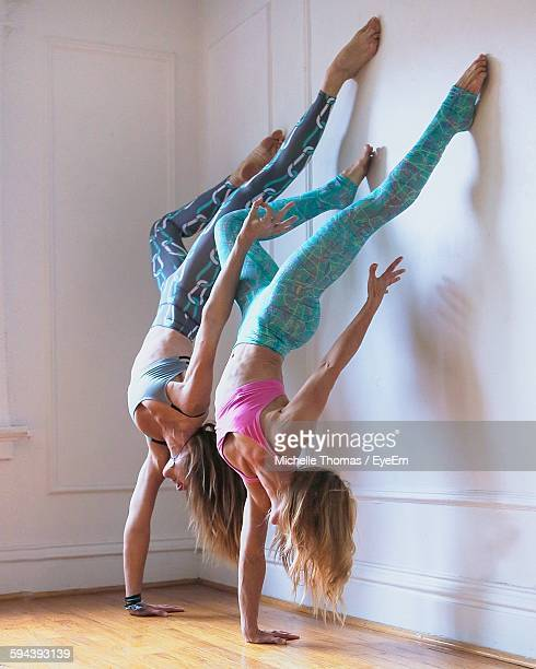 women doing handstand by wall - handstand stock pictures, royalty-free photos & images