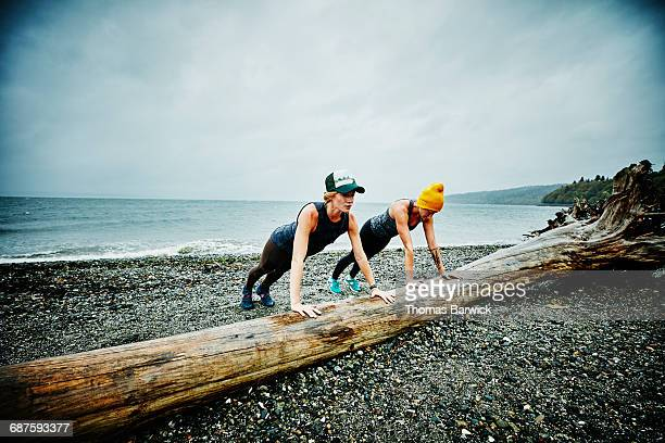 Women doing push ups on log on beach