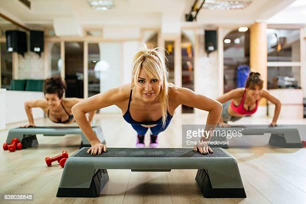 Women doing push-ups on step aerobics equipment at gym.