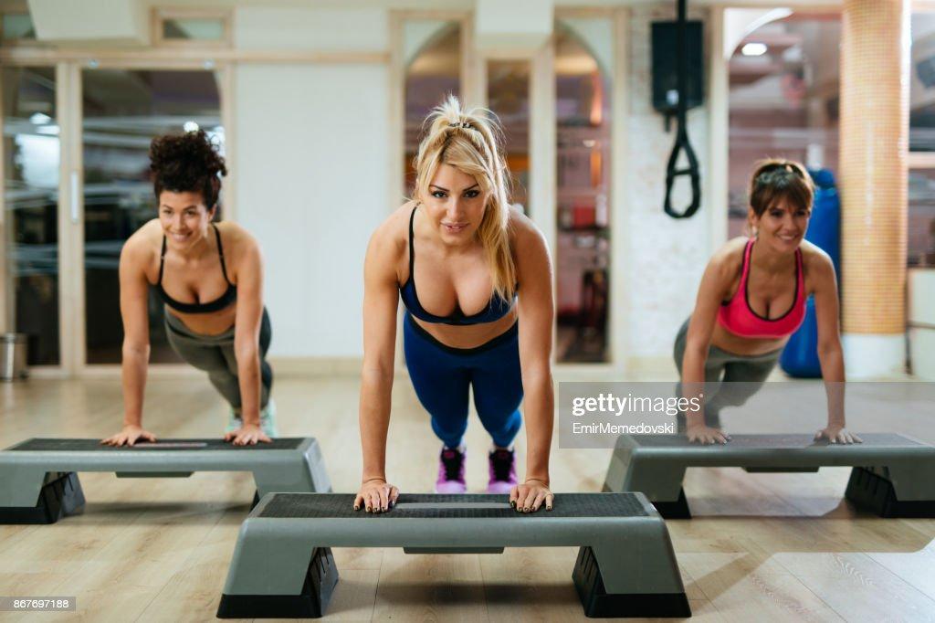 women doing pushups on step aerobics equipment at gym stock photo