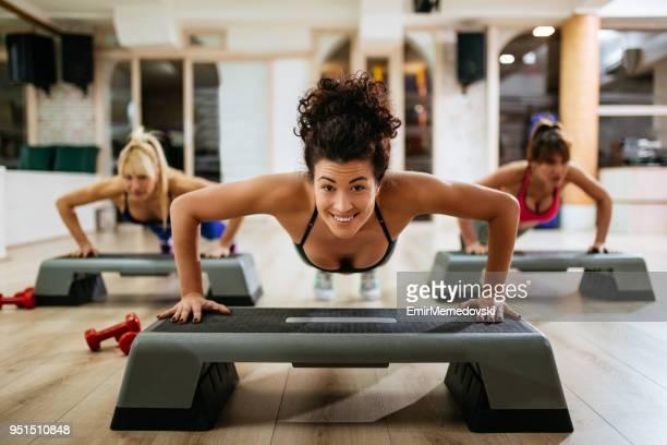 Femmes qui exécutent des Push-ups sur matériel d'aérobic step au gymnase