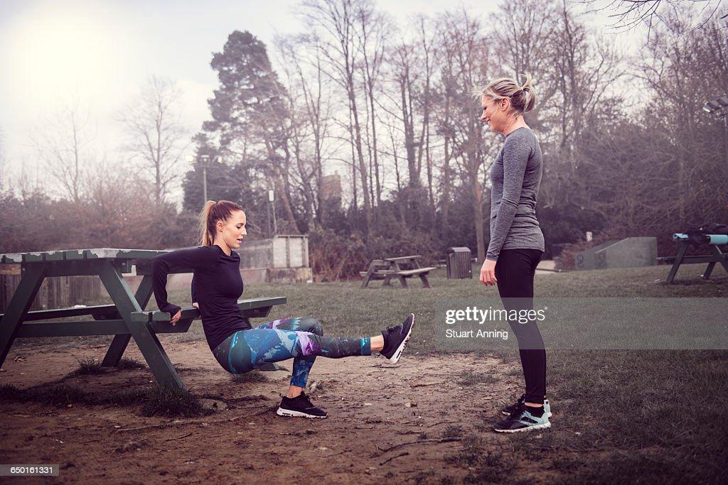 Women Doing Reverse Push Up On Picnic Bench : Stock Photo