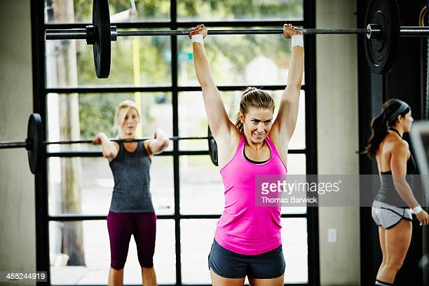 Women doing snatch with barbell in Gym gym