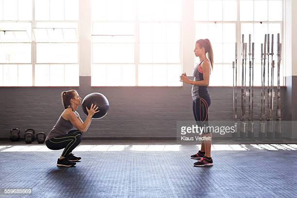 Women doing sqaud exercise with ball