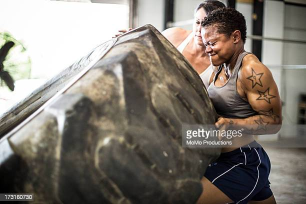 women doing tire-flip exercise - anstrengung stock-fotos und bilder