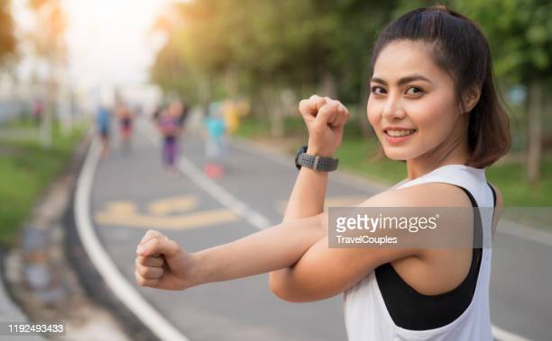 women doing warm up stretching before running or workout. female doing exercise stretching her arms. triceps and shoulders stretch wearing a smart watch activity tracker. - southeast asia stock pictures, royalty-free photos & images