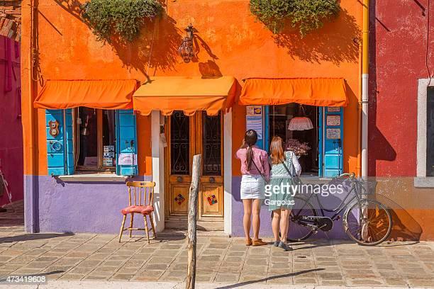 Women doing window shopping in Burano, Italy